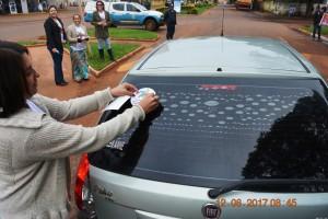 Secretária de Assistência Social, Virginia Cardoso, adesiva veículo com lema da campanha de combate ao trabalho infantil, em blitz na Avenida 13 de Maio