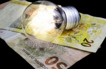 Two Brazilian Real money bank notes and a lit light bulb on top, money idea and concept