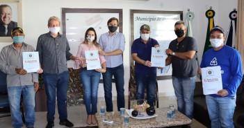 No Gabinete do Prefeito, empresários contemplados receberam os documentos de escrituras públicas assinados por Ricardo Fávaro (ao centro de boné). Foto: Roney Minella